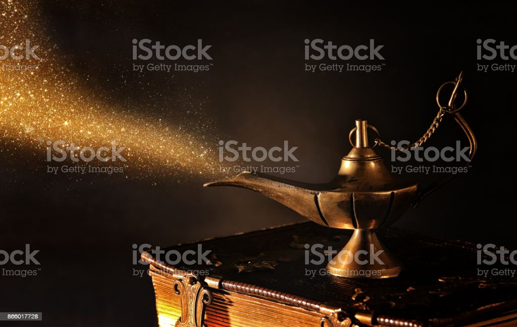 Image of magical aladdin lamp with gold glitter smoke. Lamp of wishes stock photo