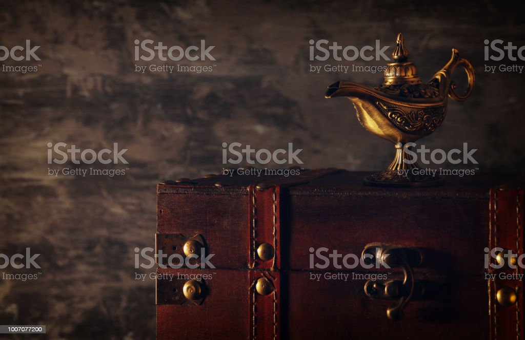 Image of magical mysterious aladdin lamp over black background. Lamp of wishes. stock photo