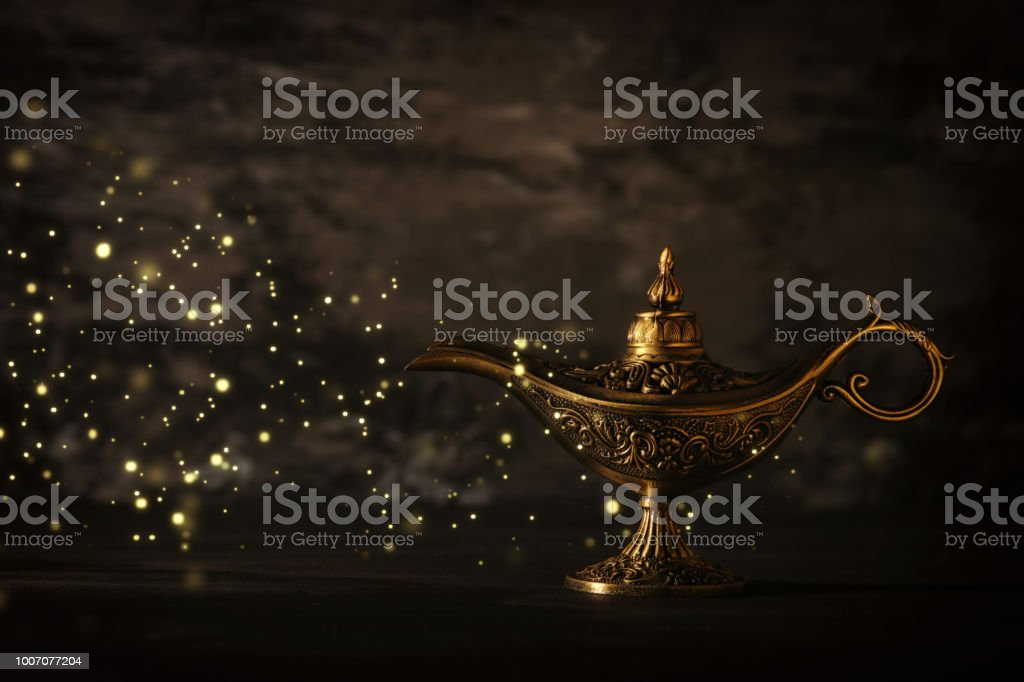 Image of magical mysterious aladdin lamp with glitter sparkle lights over black background. Lamp of wishes. stock photo