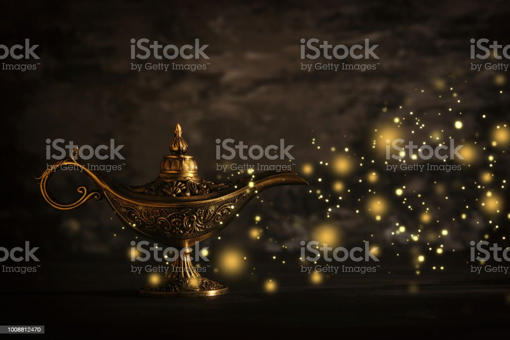 Image of magical mysterious aladdin lamp with glitter sparkle lights over black background. Lamp of wishes. стоковое фото