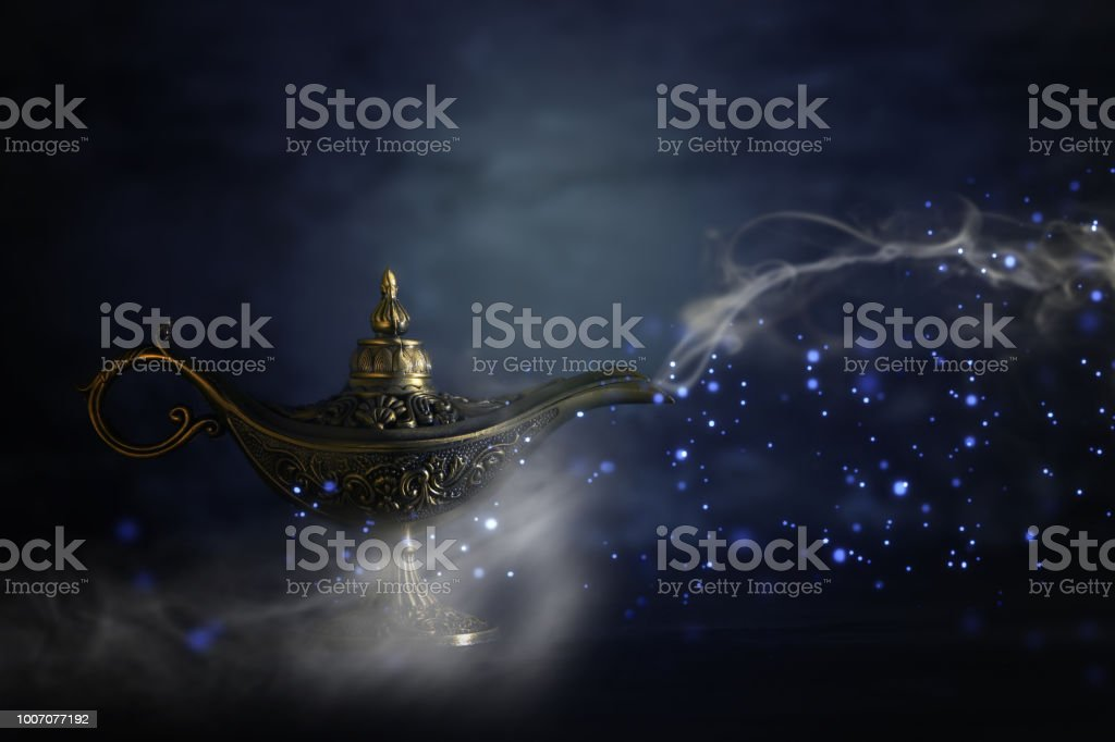Image of magical mysterious aladdin lamp with glitter sparkle smoke over black background. Lamp of wishes. stock photo
