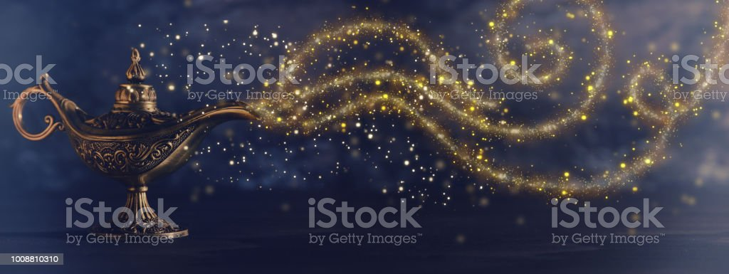 Image of magical mysterious aladdin lamp with glitter sparkle smoke over black background. Lamp of wishes. royalty-free stock photo