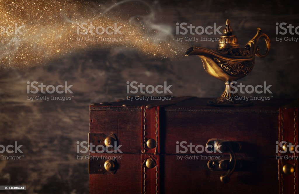 Image of magical mysterious aladdin lamp with glitter sparkle smoke over black background. Lamp of wishes. стоковое фото