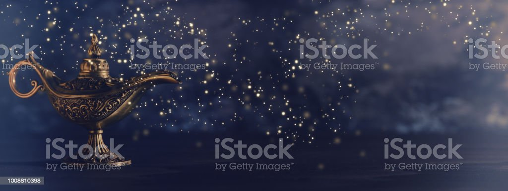 Image of magical mysterious aladdin lamp with glowing glitter lights over black background. Lamp of wishes. stock photo