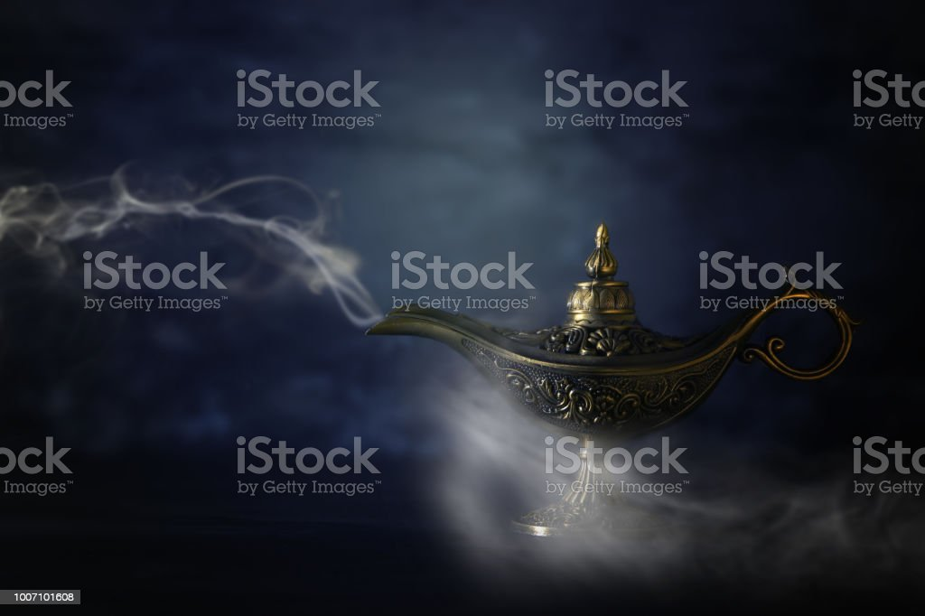 Image of magical mysterious aladdin lamp with smoke over black background. Lamp of wishes. stock photo
