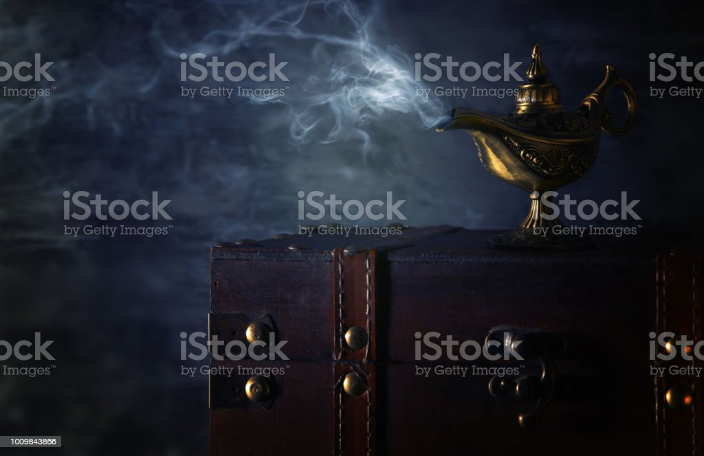 Image of magical mysterious aladdin lamp with smoke over black background. Lamp of wishes. стоковое фото