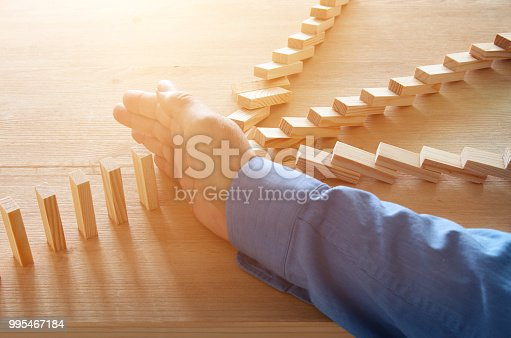 istock image of male hand stopping the domino effect. retro style image executive and risk control concept. 995467184