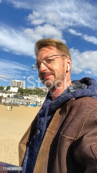Man wearing blue hoodie and brown leather jacket, taking selfies on winter out of season visit to Bournemouth Beach, Dorset, England, UK.