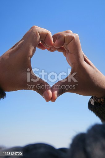 Stock Photo showing man with love heart hands forming silhouette shape against sun blue sky, heart hand shape formed with fingers above man's head as concept wallpaper photo for couple's love, romance, wedding theme with Valentine's Day heart symbol hands / fingers