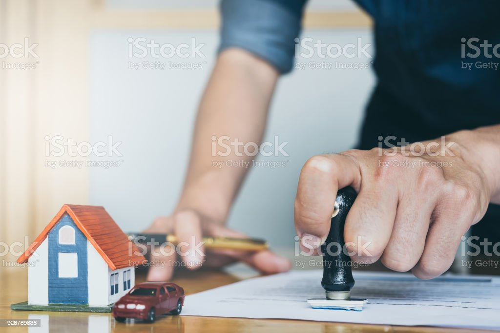 Image of Man's notary public hand stamping the document. business man, law attorney, lawyer notary public, bank manager concept. stock photo