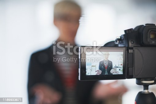 Selective focus of confident mature woman standing and talking to camera while filming a video for her internet audience about interior design.