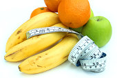 Photo showing a tape measure with fresh fruit, apples, bananas and oranges - colourful organic fresh fruit.  The fruit is pictured with a tape measure as a concept image for healthy eating, dieting, calorie counting and being overweight.