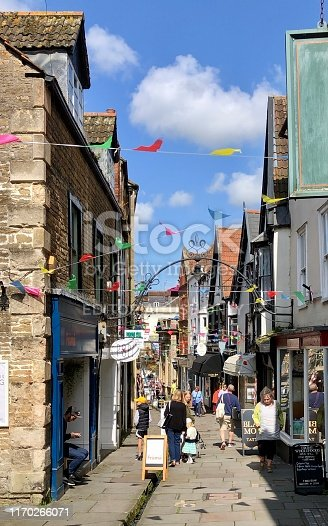 Frome, Somerset, England, UK - August, 20 2019: Image of historic medieval shops and houses lining the pedestrianised, flagstone shopping street of Cheap Street, located in the historic market town of Frome, Somerset, England. This thoroughfare is particularly unusual, as it has a narrow stream / rill running through the centre of the street, fed by a nearby natural street at the top of the hill.