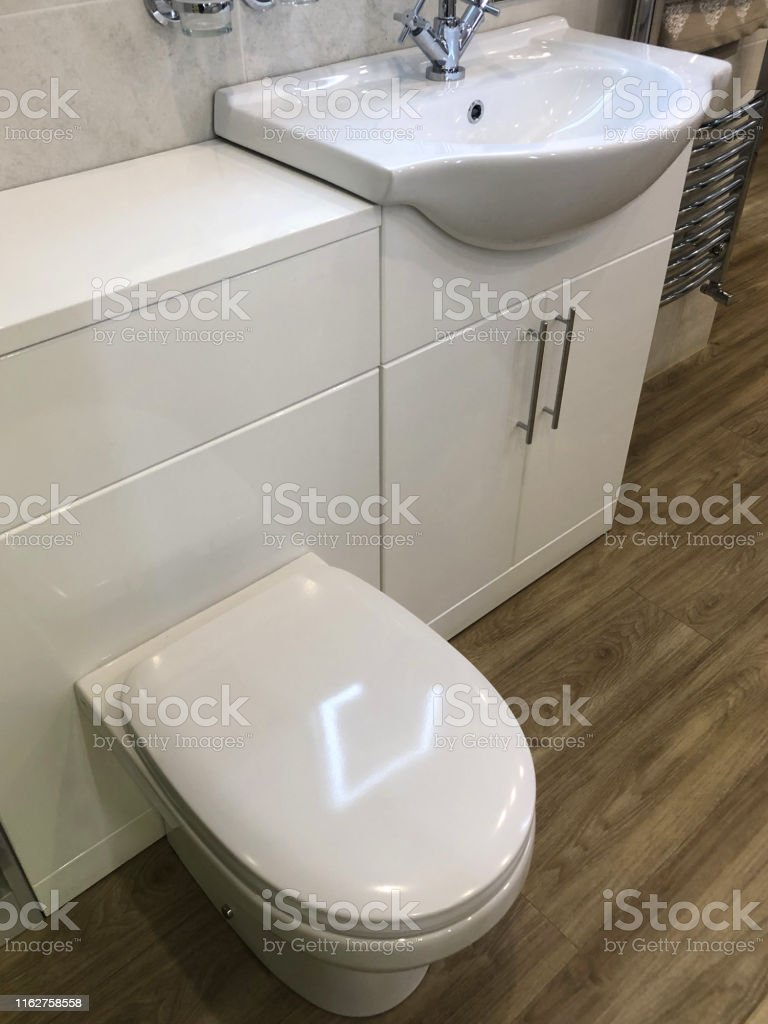 Image Of Modern Bathroom Suite With Floor White Toilet Soft Close Toilet Seat Lid Vanity Unit Cabinet Doors Sink Basin And Mixer Tap Oak Wooden Laminate Vinyl Flooring Floor And Chrome Ladder