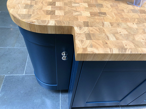 Image of modern blue kitchen curved floor cabinet cupboard with real wood worktop / countertop checkerboard butcher block pattern, wooden worktop made from oiled walnut wood end grain and stone tiled floor flooring with large rectangular slate tiles