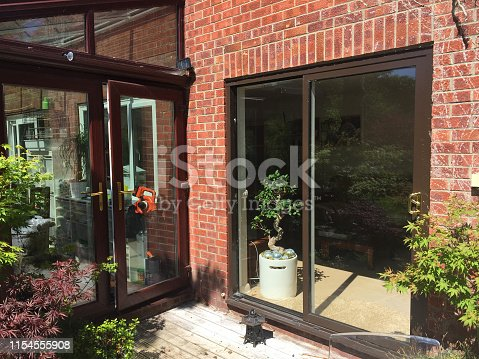 Stock photo showing modern home interior design sunny lounge double doors outside, brown painted aluminium sliding patio doors to sitting room garden view wooden decking timber patio, brown UPVC conservatory glass roof, landscaped garden outdoors eating dining area