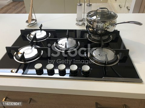 Stock photo of modern kitchen 5 burner gas hobs stove with five rings, central wok ring, white stone corian countertop / laminate worktop with saucepan cooking on hob and black glass surface, row of dials and knobs, wooden spoon holder, cabinets / cupboards