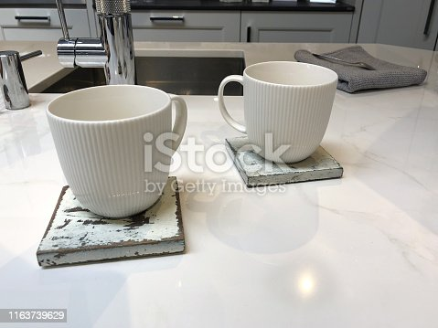 Stock photo of modern kitchen design with central island breakfast bar / kitchen table with white composite corian worktop countertop and coffee mug / distressed painted square wooden coasters set for afternoon tea, cabinets, sink and mixer tap background