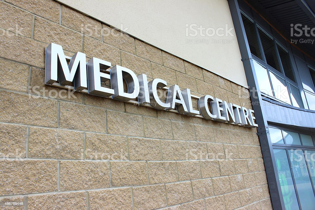 Image of modern silver Medical Centre sign, pale brick wall stock photo