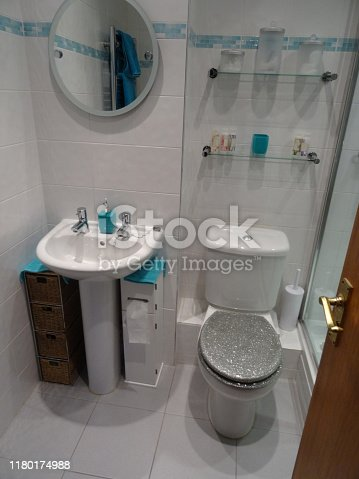 Stock photo showing a modern bathroom fitted with a rectangular glass shower enclosure and shower tray.  The bathroom features a circular mirror hung over a pedestal sink basin, with chrome  taps and a white tiled floor.  The white tiles of the bathroom giving it  contemporary feel.