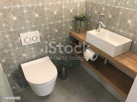 Stock Photo of modern white luxury washroom / bathroom cloakroom WC suite with contemporary curved wall hung toilet pan hanging on washroom wall, small rectangular sink basin, single chrome mixer tap on wooden shelf surface, toilet roll, brush, patterned tiles