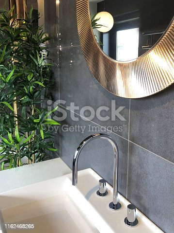 Stock Photo of modern white luxury washroom bathroom suite with ceramic rectangular sink basin and chrome mixer tap, contemporary large grey rectangular stone tiles / round copper mirror hanging on washroom wall, artificial bamboo plant with fake plastic leaves