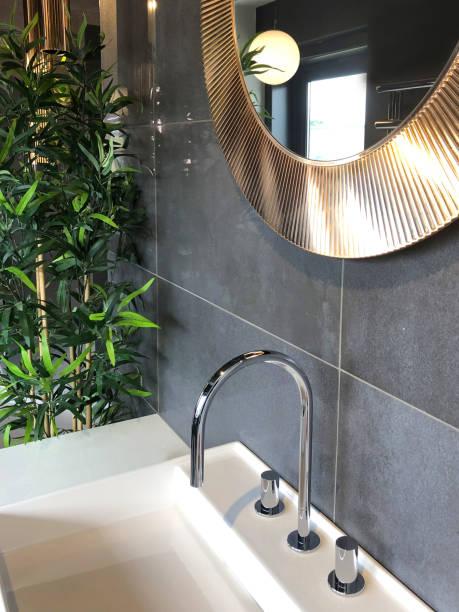 Bild von modernen weißen Luxus Waschraum Badezimmer Suite mit Keramik rechteckige Waschbecken und Chrom Mixer Hahn, moderne große große graue rechteckige Steinfliesen / runde KupferSpiegel hängen an Waschraum Wand, künstliche Bambuspflanze mit gefäls – Foto