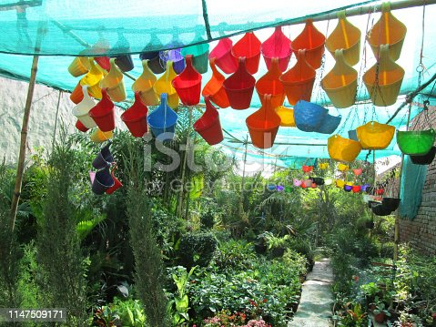 Stock photo of colourful plastic hanging flower pots, in rainbow colours, which are designed to hang from balconies, in Indian garden centre, with palm trees, flowering plants, net shading.