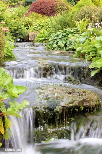 Stock photo of natural garden waterfall water feature connecting two ponds in landscaped oriental garden with long exposure water photography on camera / slow shutter speed to make fast flowing water blue blurred cascading over rocks, rockery plants and stream