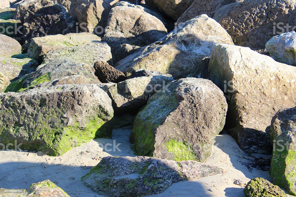Image of natural riprap sea defence on sand, rock armour stock photo