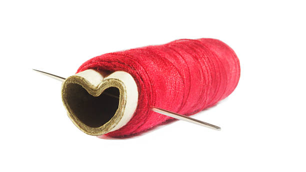 Image of needle through spool Image of needle through heart shape spool red broken heart sewn threads stock pictures, royalty-free photos & images