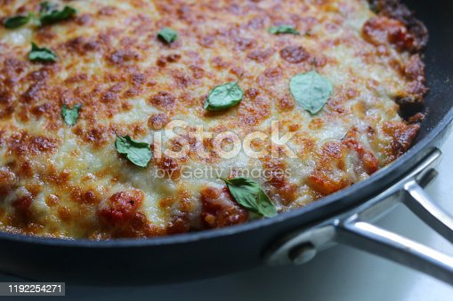 Stock image showing a ready to eat 'meatza'. This is a pizza style meal which uses minced meat as a base, instead of dough, topped with melted cheese and basil leaves.