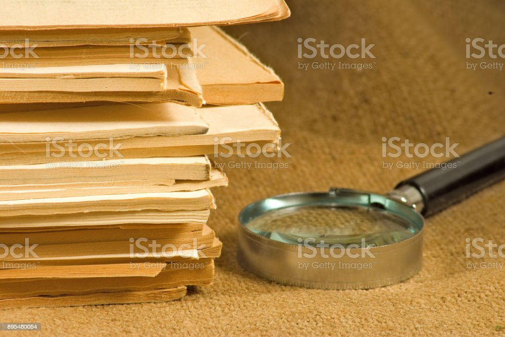 image of notebooks, magazines and magnifying glass on a table close-up stock photo