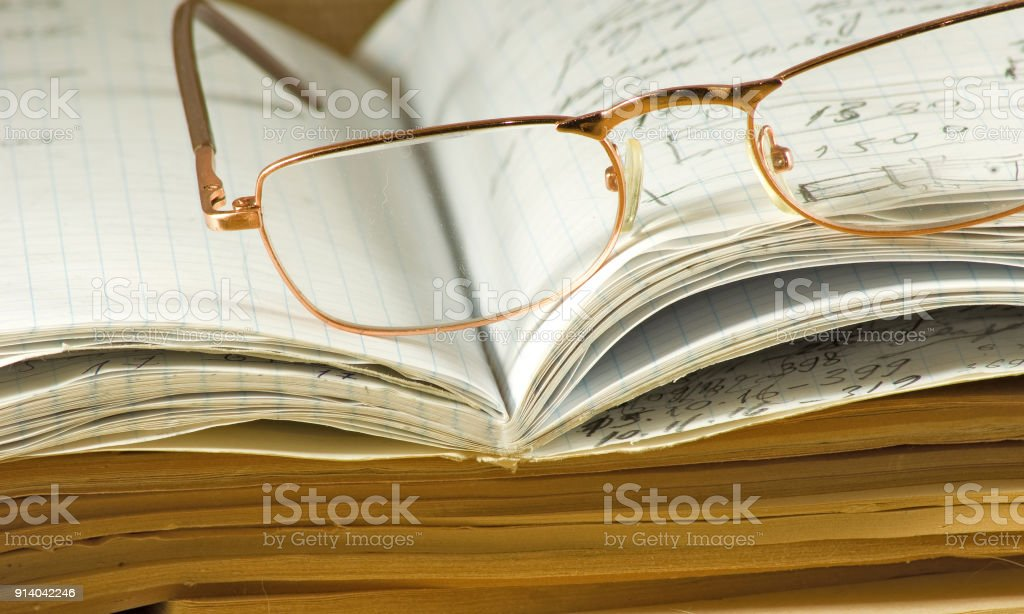 image of notebooks, magazines, glasses  on a table closeup stock photo
