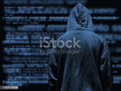 Stock photo of obscured secret computer hacker programmer youth wearing hoodie with dark programming computer code background, concept for cyber war hacking technology, encryption coding, Internet crime, software programming, digital data analysis