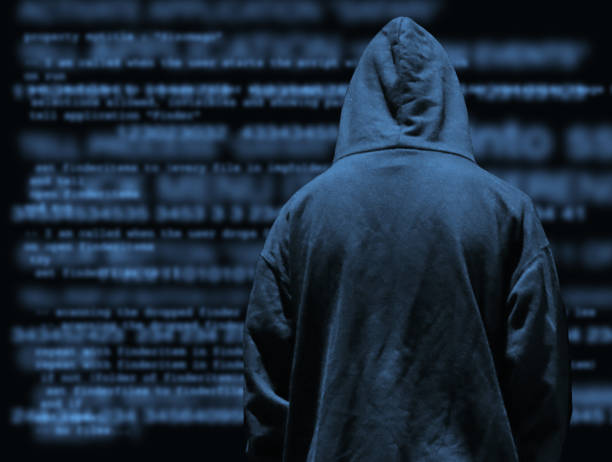 Image of obscured secret computer hacker programmer youth wearing hoodie with dark programming computer code background, concept for cyber war hacking technology, encryption coding, Internet crime, software programming, digital data analysis stock photo
