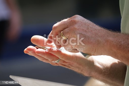 Stock photo of old man paying for goods at street market shop using coins currency and paper notes as money to pay, holding coins in hand and counting money in palm with fingers, old hairy hands, freckles and rings outside in sunshine, monetary payment photo
