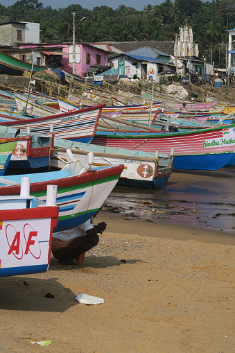 Fishing Beach Harbour, Kovalam, Kerala, South India - March, 31 2019: \nStock photo of old wooden Indian fishing boats and canoes kayaks at Kovalam Beach, painted white, pink, green and blue with flaking paint and sea harbour view. Fisherman hiding crouched behind boat in order to shit / defecate at water's edge.
