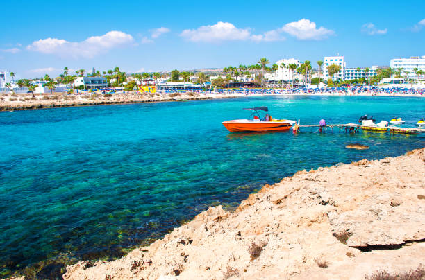 image of one red speedboat in the bay of vathia gonia beach near agia napa, cyprus. rocky coast and sea with turquoise blue water in a bay, houses on the background. warm day in fall - cyprus стоковые фото и изображения