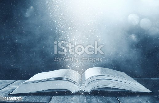 istock image of open antique book on wooden table with glitter background 1015855272