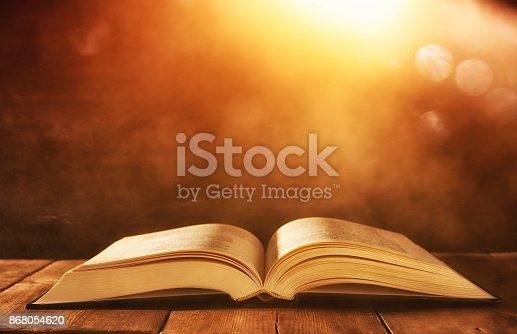 istock image of open antique book on wooden table with glitter background 868054620