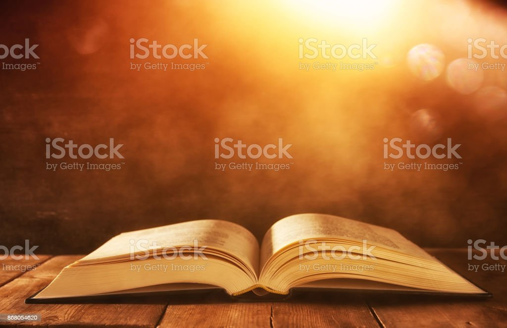 image of open antique book on wooden table with glitter background stock photo