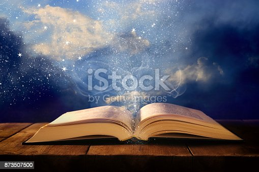 istock image of open antique book on wooden table with glitter overlay. 873507500