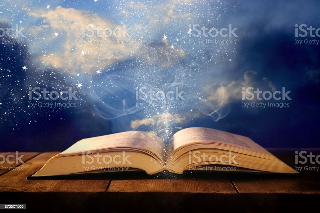 image of open antique book on wooden table with glitter overlay. - fotografia de stock