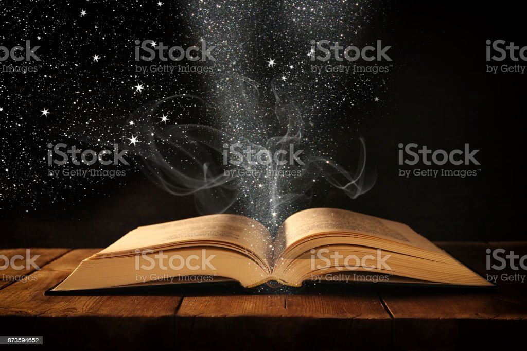 image of open antique book on wooden table with glitter overlay. stock photo