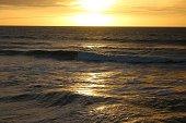 Stock photo showing horizon over water, highlighted by an orange sunset over Mahatma Ghanaian Beach / Fort Kochi Beach, Kochi / Cochin, Kerala, India.
