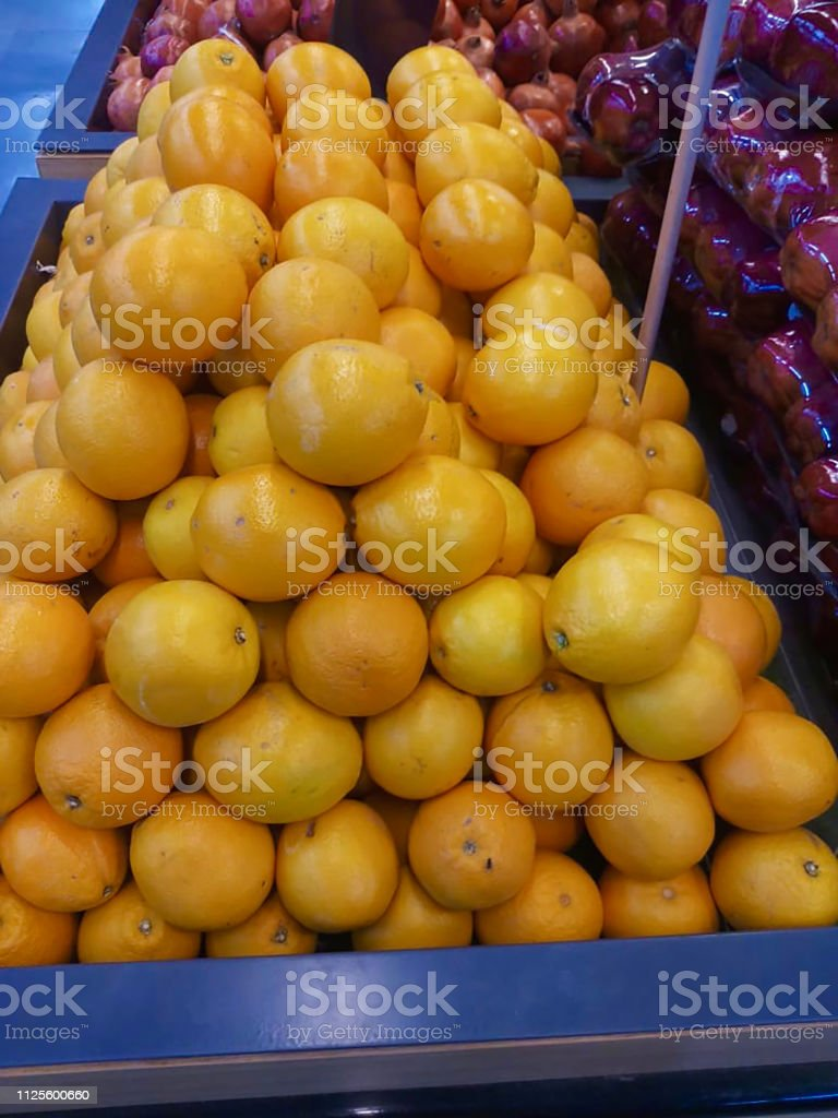 Pyramid display of a pile of oranges in a supermarket in India.