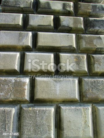 Photo showing rectangular, large ornamental Bath stone bricks / brickwork with bevelled edging.  A combination of weathering, grime and dirt caused by pollution, and shadows are highlighting the outlines and shapes of the blocks on this unusual brick wall.
