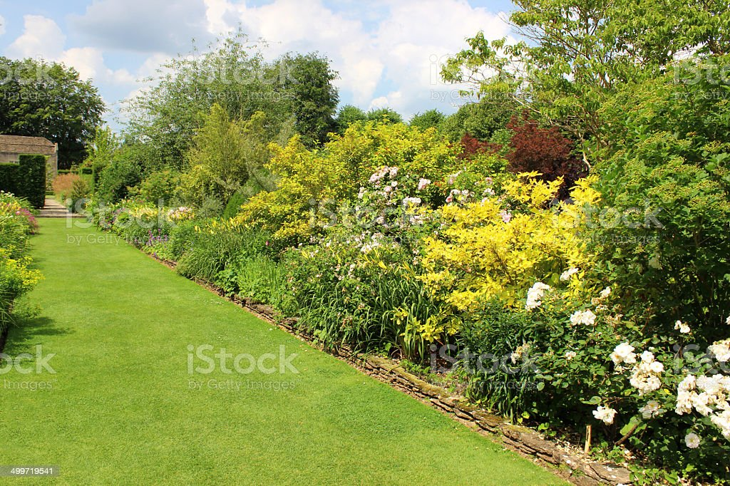 Image of ornamental flower garden with lawn pathway, herbaceous plants royalty-free stock photo
