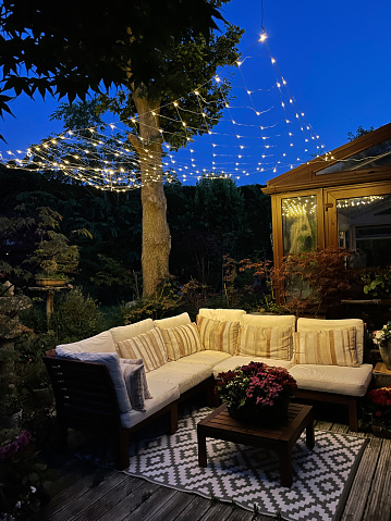 Stock photo showing ornamental Japanese-style garden with outdoor lounge area at night illuminated with fairy lights. Featuring crystal clear koi pond, whitewashed, grooved timber decking patio, Japanese bonsai maples and hardwood, cushion covered seating.